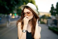 户外一个白色帽子和太阳镜的年轻美丽的妇女在一个城市在夏天 免版税库存图片