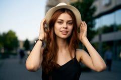 户外一个白色帽子的年轻美丽的妇女在一个城市在夏天 库存图片