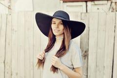 户外一个美丽的深色的女孩的画象在帽子,生活方式 免版税库存图片