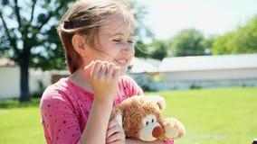 户外一个逗人喜爱的小女孩的画象 一个小女孩微笑着 股票视频