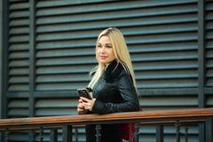 户外一件黑夹克的美丽的女孩 库存照片