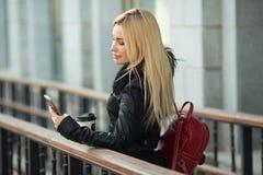 户外一件黑夹克的美丽的女孩 免版税库存图片