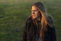 户外一名妇女的画象日落的 绿色背景 免版税库存图片