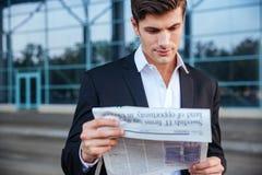 户外一张英俊的商人读书报纸的画象 库存照片