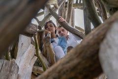 户外一起年轻夫妇在乡下的木背景 库存图片