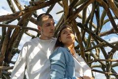 户外一起年轻夫妇在乡下的木背景 库存照片