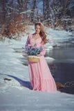 户外一件桃红色礼服的美丽的金发碧眼的女人在冬天 免版税库存图片