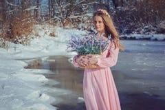 户外一件桃红色礼服的美丽的金发碧眼的女人在冬天 免版税图库摄影