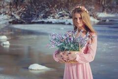 户外一件桃红色礼服的美丽的金发碧眼的女人在冬天 免版税库存照片