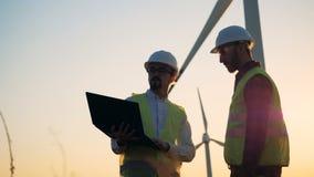 户外与两名男性工作者的风车驻地有交谈在它附近 替代背景概念数字式能源例证太阳风 股票录像
