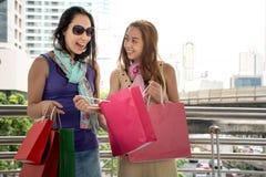 户外两个时尚五颜六色的顾客画象获得乐趣与袋子购物一起 库存图片