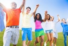 户外举行手庆祝的不同种族的少年 免版税图库摄影