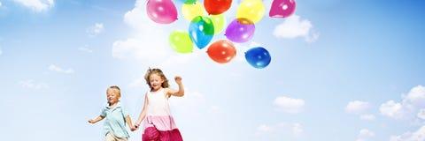 户外举行气球概念的小女孩和男孩 免版税库存图片