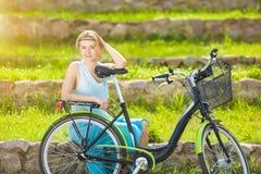 户外享受与自行车的美丽的白肤金发的妇女自然 免版税图库摄影