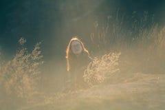 户外享受自然的秀丽女孩 有长的健康吹的头发的运行在春天领域的,太阳美丽的少年式样女孩 免版税库存图片