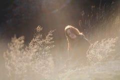 户外享受自然的秀丽女孩 有长的健康吹的头发的运行在春天领域的,太阳美丽的少年式样女孩 免版税图库摄影