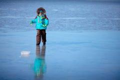户外使用在冻海的逗人喜爱的小男孩 图库摄影