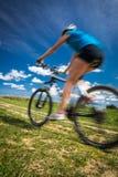 户外俏丽,年轻女性骑自行车的人在她的登山车 库存照片