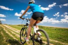 户外俏丽,年轻女性骑自行车的人在她的登山车 免版税库存照片
