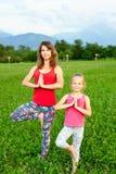 户外做瑜伽的母亲和她的女儿 图库摄影