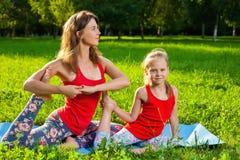 户外做瑜伽的母亲和她的女儿 库存图片
