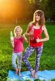 户外做瑜伽的母亲和她的女儿 库存照片