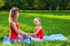 户外做瑜伽的母亲和她的女儿 免版税库存照片