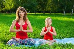 户外做瑜伽的母亲和她的女儿 免版税库存图片