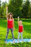 户外做瑜伽的母亲和她的女儿 免版税图库摄影