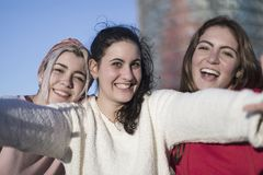 户外做selfie的三个愉快的最佳的女朋友在smartphon 库存图片
