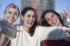 户外做selfie的三个愉快的最佳的女朋友在smartphon 图库摄影