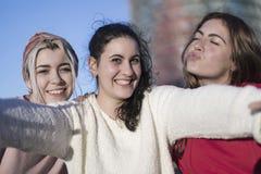 户外做selfie的三个愉快的最佳的女朋友在smartphon 免版税库存照片