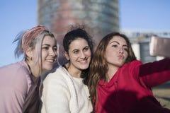 户外做selfie的三个愉快的最佳的女朋友在smartphon 库存照片