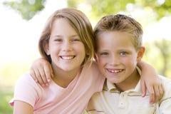 户外兄弟姐妹坐的微笑 库存图片