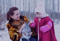 户外兔子野兔下雪逗人喜爱的孩子一点双亲童年微笑的幼儿幸福妇女冬天婴孩冬天家庭ch 免版税库存照片
