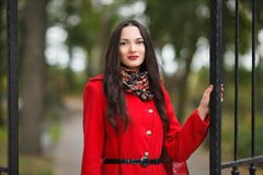 户外典雅和时髦的看起来的年轻可爱的新鲜的看起来的深色的妇女生活方式画象有红色嘴唇的在红色外套p 库存照片
