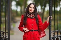 户外典雅和时髦的看起来的年轻可爱的新鲜的看起来的深色的妇女生活方式画象有红色嘴唇的在红色外套p 库存图片
