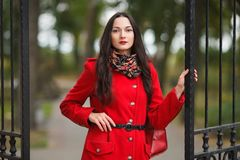 户外典雅和时髦的看起来的年轻可爱的新鲜的看起来的深色的妇女生活方式画象有红色嘴唇的在红色外套p 免版税库存图片