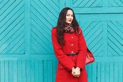 户外典雅和时髦的看起来的年轻可爱的新鲜的看起来的深色的妇女生活方式画象有红色嘴唇的在红色外套t 免版税库存图片
