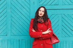 户外典雅和时髦的看起来的年轻可爱的新鲜的看起来的深色的妇女生活方式画象有红色嘴唇的在红色外套t 免版税库存照片