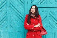 户外典雅和时髦的看起来的年轻可爱的新鲜的看起来的深色的妇女生活方式画象有红色嘴唇的在红色外套t 库存照片