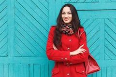 户外典雅和时髦的看起来的年轻可爱的新鲜的看起来的深色的妇女生活方式画象有红色嘴唇的在红色外套t 免版税图库摄影