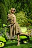 户外减速火箭的妇女与一辆绿色滑行车 库存图片