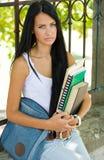 户外华美的新深色的学员女孩。 免版税图库摄影