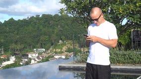 户外发短信在他巧妙的电话的英俊的年轻人画象,当站立在屋顶无限游泳池时 影视素材