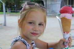 户外吃冰淇凌的女孩 免版税库存图片
