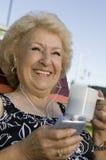 户外听便携式音乐播放的资深妇女举行杯子微笑。 图库摄影