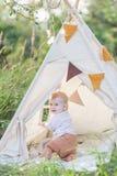 户外圆锥形帐蓬的一个年逗人喜爱的男孩 免版税图库摄影