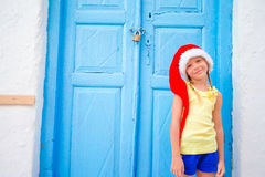户外圣诞老人帽子的小女孩在老街道圣诞节假期在米科诺斯岛 在典型的希腊语街道的孩子  图库摄影