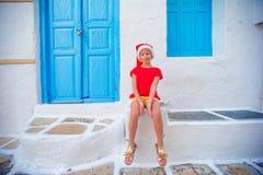 户外圣诞老人帽子的小女孩在老街道圣诞节假期在米科诺斯岛 在典型的希腊语街道的孩子  免版税库存图片